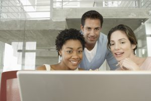 Two Woman and a Man Looking at a Laptop Screen