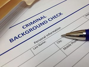Page saying Background Check with a pen on it