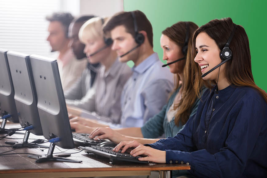 Call center employees smiling at computers